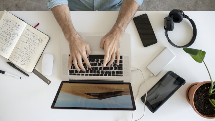 Top view of man using laptop at desk in office model released Symbolfoto property released PUBLICATIONxINxGERxSUIxAUTxHU
