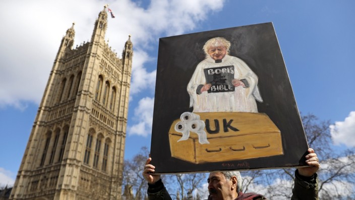 Artist Kaya Mar holds a painting depicting Britain's Prime Minister Boris Johnson, outside Houses of Parliament, following an outbreak of the coronavirus, in London