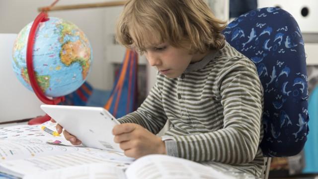 Junge Grundschüler 8 Jahre alt lernt zuhause für die Schule macht Hausaufgaben lernt mit einem