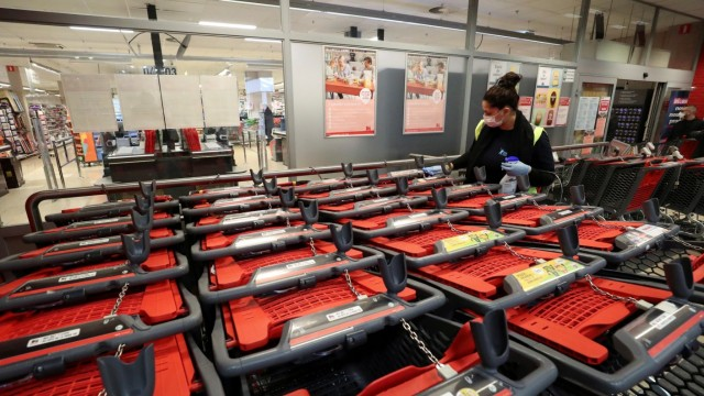 A worker disinfects shopping carts of a supermarket before Belgium government imposes a coronavirus lockdown in Brussels