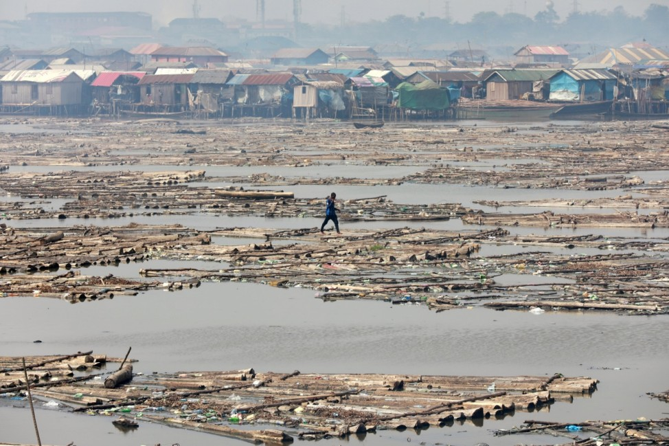 A man walks on logs of wood placed on the river at the Makoko community in Lagos