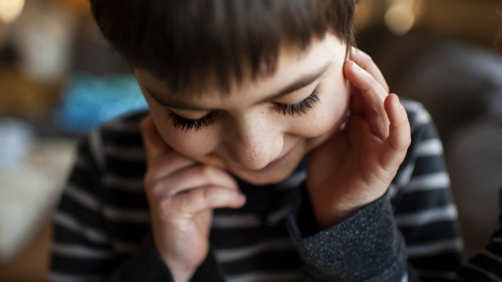 Boy 7-8 years old with long eyelashes looking down with hands by face United States, Iowa, Grimes PUBLICATIONxINxGERxSUI