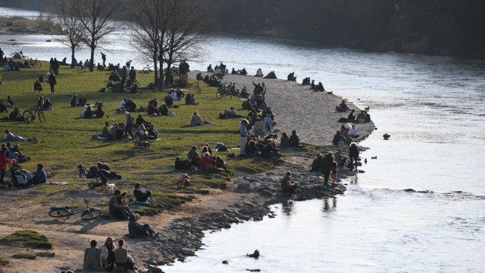 People sitting at the riverside of Isar enjoy the sun in Munich