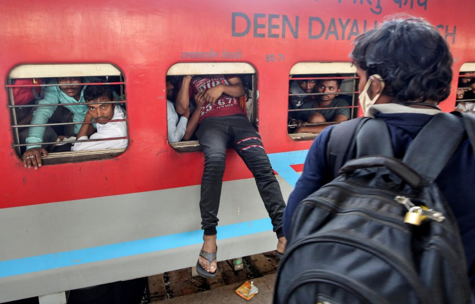 A migrant worker tries to board an overcrowded passenger train from an emergency window, after government imposed restrictions on public gatherings in attempts to prevent spread of coronavirus disease, in Mumbai