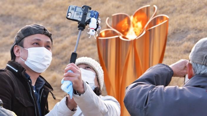 People take photos of the Olympic Flame at Ishinomaki Minamihama Tsunami Recovery Memorial Park, Ishinomaki, Miyagi-pref