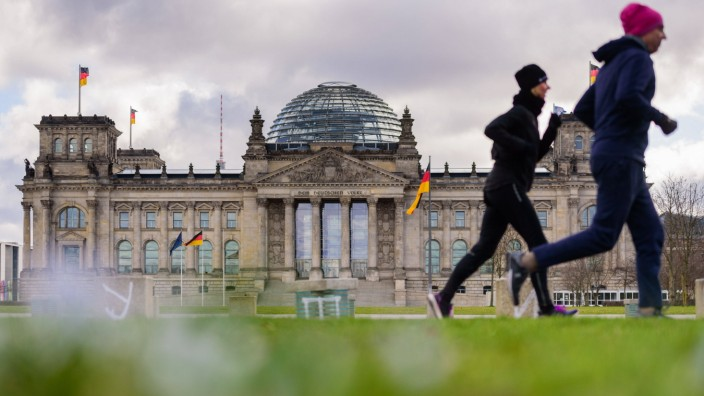 March 21, 2020: Two joggers pass the empty Platz der Republik in front of the German Reichstag. The Governing Mayor of B