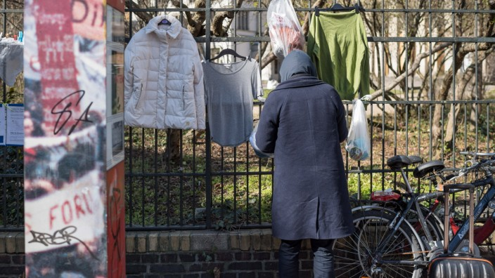 Ein Obdachloser nimmt Lebensmittel vom Spendenzaun an der Evangelische Kirchengemeinde am Weinberg in Berlin-Mitte (Fot