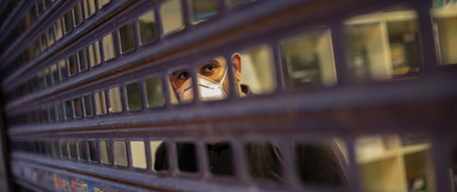 Coronavirus in Spanien: Ein Mann hinter einem Gitter in Madrid. Mehr als die Hälfte der Corona-Toten in Spanien entfällt auf die Hauptstadt.