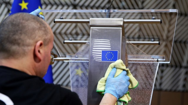A man disinfects a desk before a news conference of European Council President Charles Michel in Brussels