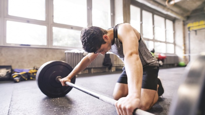 Young athlete exercising with barbell in gym model released Symbolfoto property released PUBLICATION; Fitness