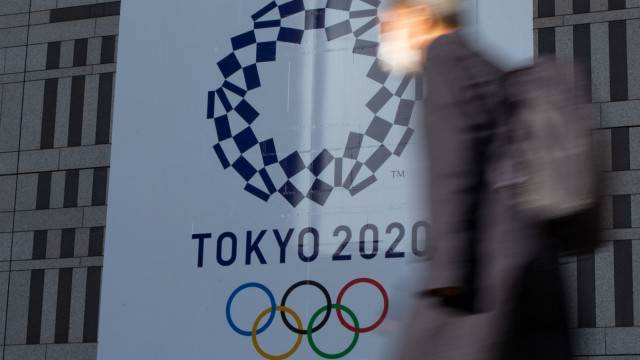A man walks past a large display promoting the Tokyo 2020 Olympics in Tokyo, Japan on March 25, 2020, a day after the T; Tokio Olympia