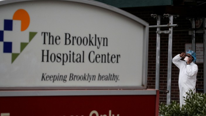 A health worker in protective gear speaks on the phone outside the Brooklyn Hospital Center, during the coronavirus disease (COVID-19) outbreak in Brooklyn, New York