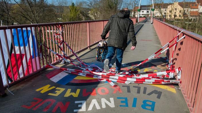Ein Mann passiert einen Grenzübergang zwischen Frankreich und dem Saarland.