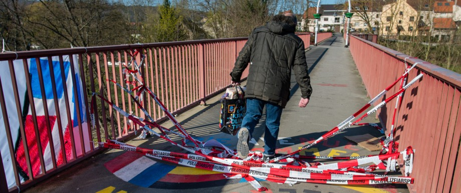 A man passes a border crossing between France and Saarland.