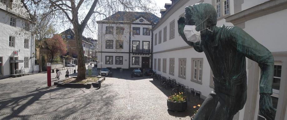 Eine wasserspeiende Brunnenfigur vor dem historischen Rathaus von Koblenz trägt einen Mundschutz.