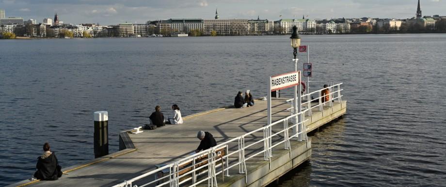 Nur wenige Menschen sitzen in Hamburg an der Außenalster.