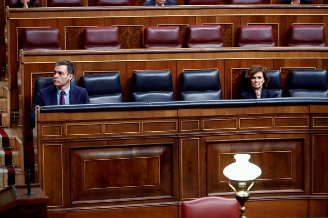 Spanish PM Sanchez sits near Deputy PM Calvo before speaking on coronavirus disease (COVID-19) at Parliament in Madrid