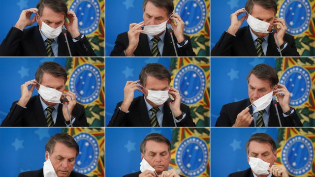 Brazil's President Jair Bolsonaro adjusts his protective face mask during a press statement to announce federal judiciary measures to curb the spread of the coronavirus disease (COVID-19) in Brasilia