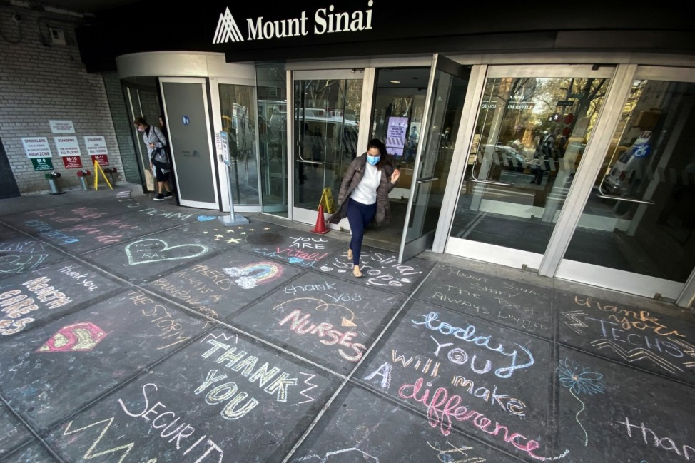 Woman exits Mount Sinai Hospital past messages of thanks to healthcare workers written on sidewalk in New York