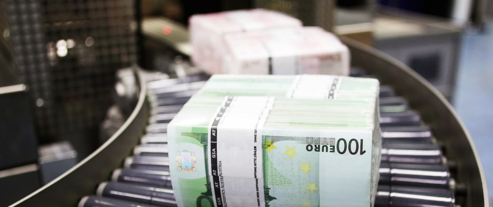 Bundles of euro banknotes move along a conveyer belt at the GSA Austria company's headquarters in Vienna