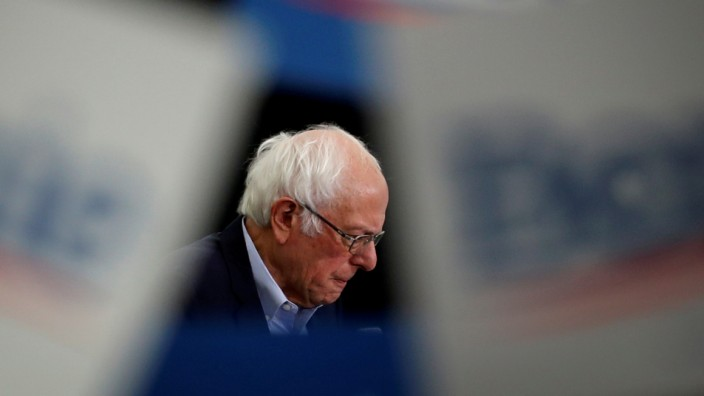 FILE PHOTO: Democratic U.S. presidential candidate Senator Bernie Sanders is seen as supporters wave signs as he speaks at a campaign rally in Milford