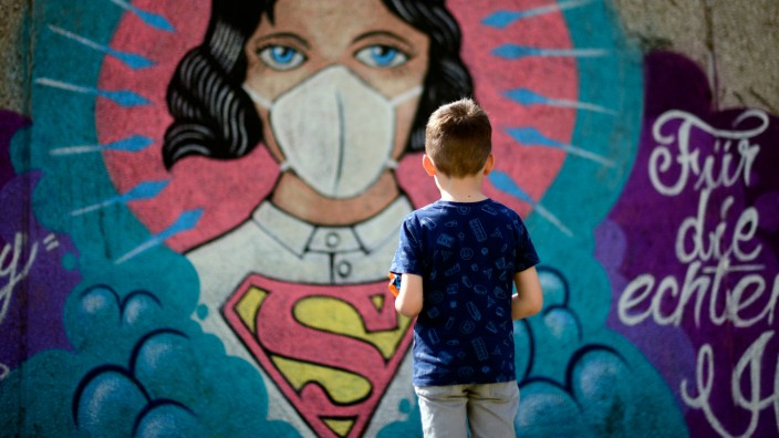 Corona in Deutschland: Ein Junge steht vor einem Graffiti in Hamm