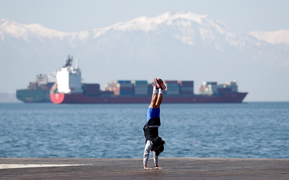 A woman stretches seaside promenade as the coronavirus disease (COVID-19) outbreak continues, in Thessaloniki