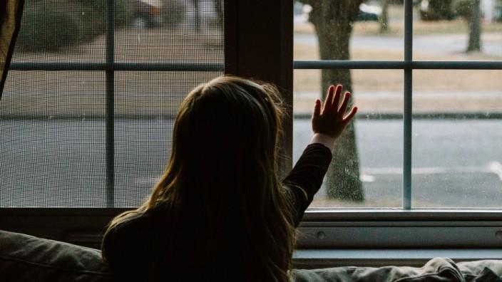 A little girl touches her living room window. Garden City South, New York, USA. PUBLICATIONxINxGERxSUIxAUTxONLY CR_FRRU1