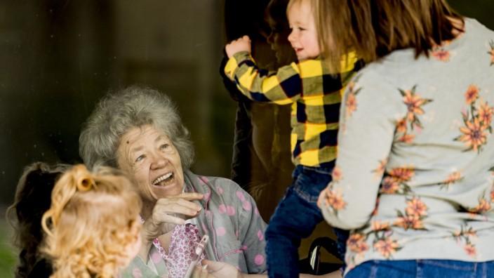 Coronavirus: Angehörige besuchen Senioren im Pflegeheim getrennt durch eine Glasscheibe