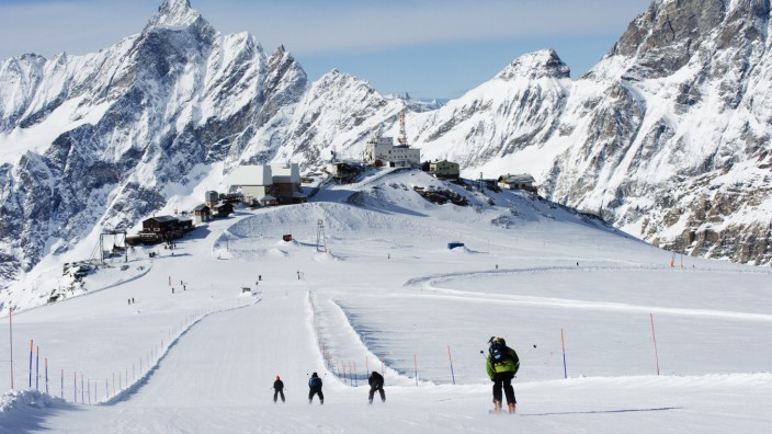 Skiers skiing on a ski run mountain scenery in Cervinia ski resort Cervinia Valle d Aosta Italia