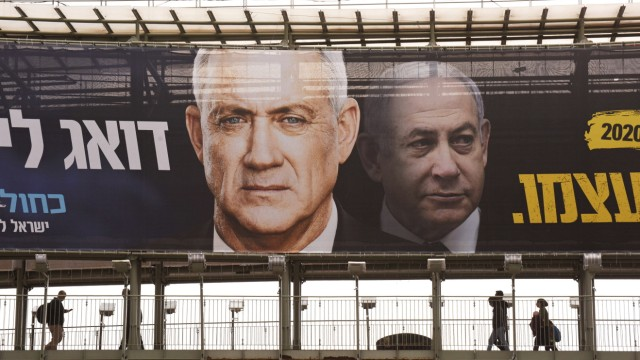 Israelis walk on a bridge beneath election campaign posters for Benny Gantz s Blue and White Party, on Monday, February