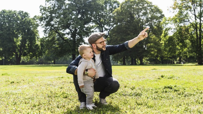 Father talking to son in a park model released Symbolfoto PUBLICATIONxINxGERxSUIxAUTxHUNxONLY UUF138