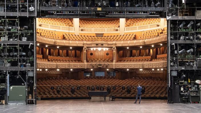 Ein Mitarbeiter der Staatstheater Stuttgart steht auf der Bühne des Opernhauses der Staatstheater Stuttgart, im Hintergrund ist der Zuschauerraum zu sehen.