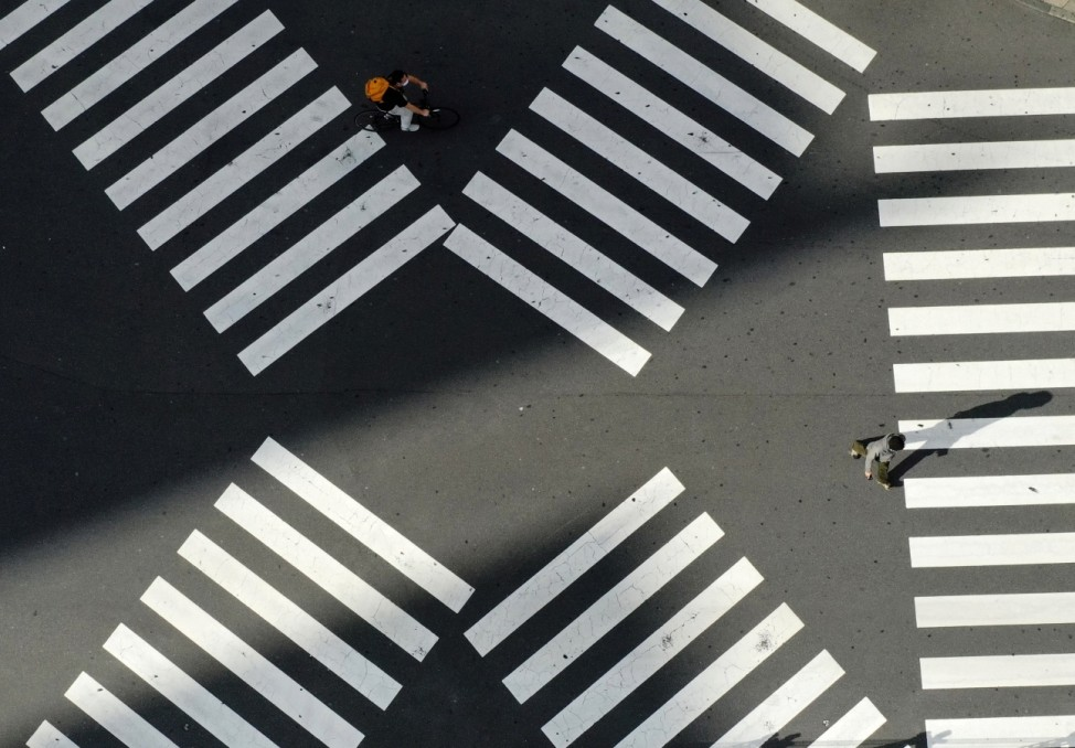 A man crosses a street in front of Shinjuku station in Tokyo