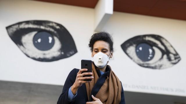 Corona-Krise: Frau mit Mundschutz schaut auf ihr Handy