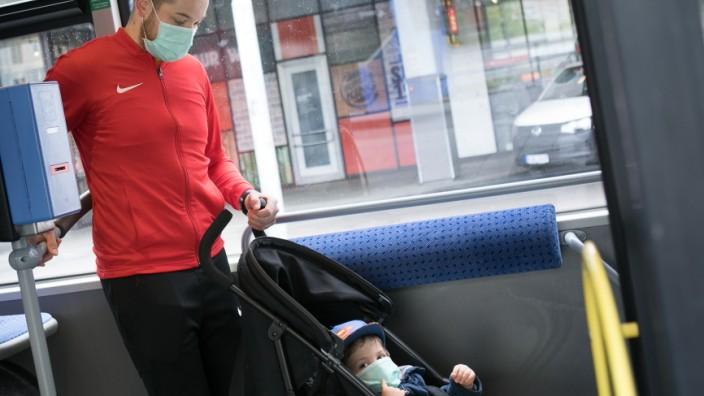 Vater und Sohn tragen Masken im Bus der MVV.