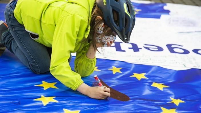 Ein Kind malt ein Herz in einer Europäische Flagge