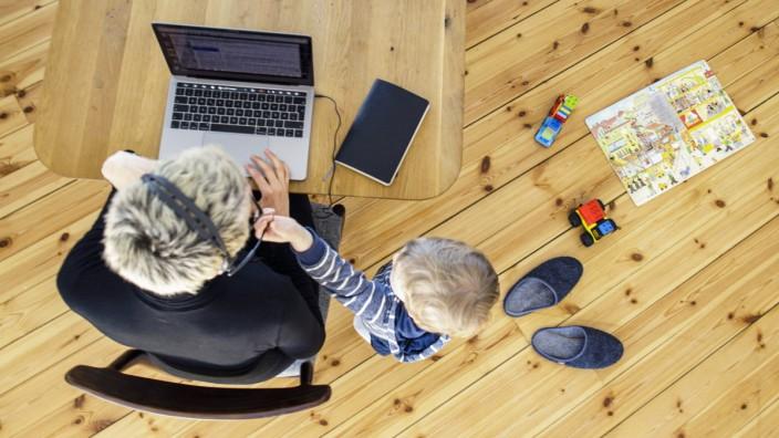 Symbolfoto zum Thema Homeoffice. Eine Frau sitzt zu Hause am Schreibtisch und arbeitet. Neben ihr spielt ein Kind. Berli