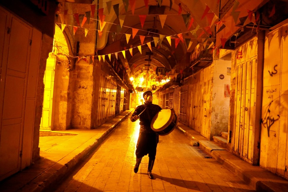 Palestinian Musharati wake Muslims up to have the predawn meal before they start their long-day fast during Ramadan in Nablus
