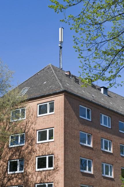 Mobilfunkmast auf dem Dach eines Wohnhauses Mobilfunkmast Sendemast Mobilfunksender Mobilfunkantenne mobile Kommunikatio