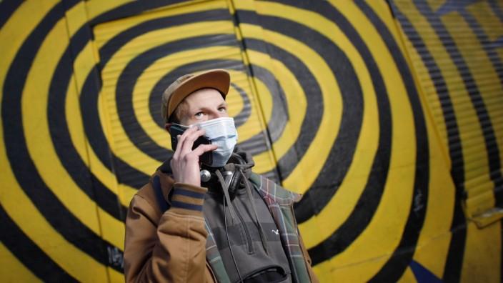 Coronavirus App - Ein Passant mit Mundschutz posiert mit seinem Handy vor einem Grafitti an einem Club. Köln, 06.04.2020 A passer-by w
