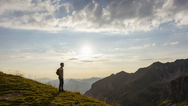 Germany Bavaria Oberstdorf man on a hike in the mountains looking at view at sunset model release