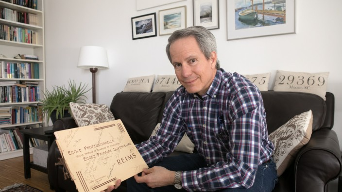 Doug Claus in seiner Wohnung in der Olympia-Pressestadt. Sein Vater war bei der Unterschrift zur Kapitulation in Reims am 7. Mai 1945 als Büromitarbeiter Eisenhowers vor Ort und hat als persönliches Souvenir auf dem Cover eines Schul-Bilderbuchs 30 Unte