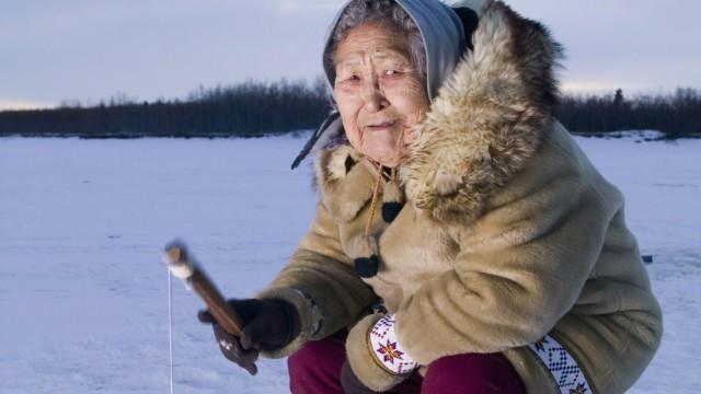 Elder Native Yupik Female Sits On Stump Ice Fishing Kuskokwim River Tuluksak Western Alaska Winter P