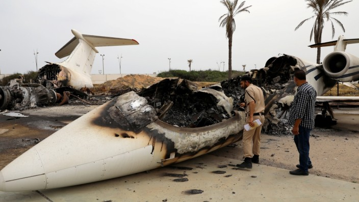 A policeman and a man inspect a passenger plane damaged by shelling at Tripoli's Mitiga airport in Tripoli