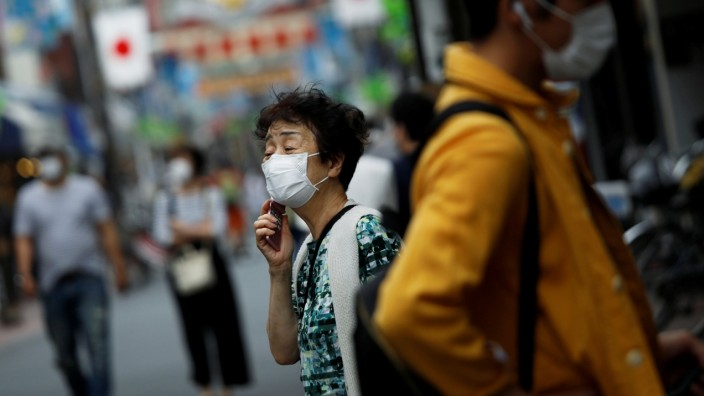 People wearing protective face masks walk on the street under a nationwide state of emergency as the spread of the coronavirus disease (COVID-19) continues in Tokyo