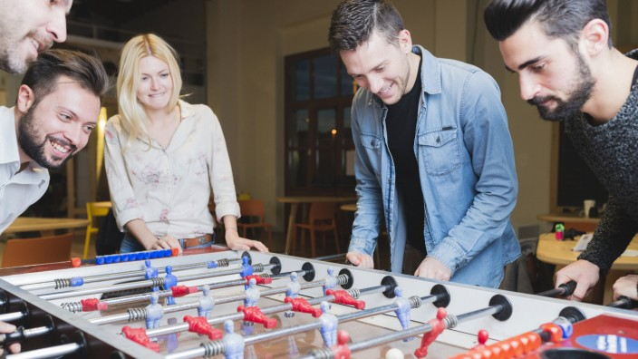 Happy colleagues playing foosball in office model released Symbolfoto property released PUBLICATION
