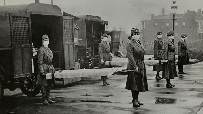 FILE PHOTO: Mask-wearing women hold stretchers near ambulances during the Spanish Flu pandemic in St. Louis