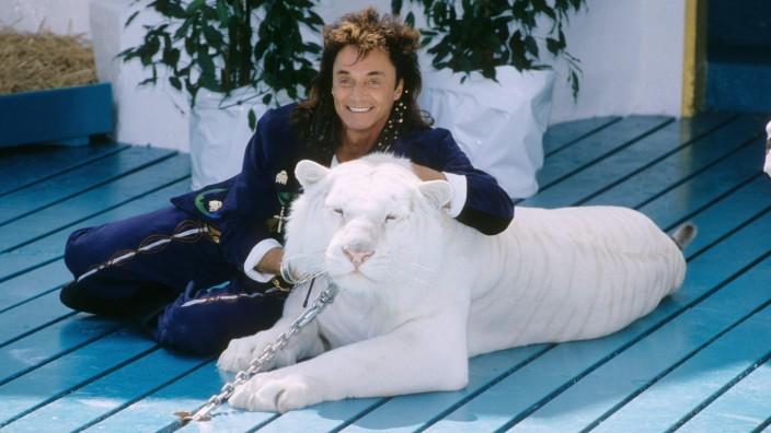 Roy (Siegfried & Roy) mit weißem Tiger 06/91 nou quer ganz kniend lächelnd Mikrophon leger Anzug blau Mann langhaarig d