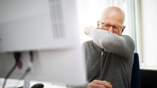 Gestellte Aufnahme zum Thema: Erkaeltung im Buero. Ein Mann niest in seine Armbeuge, Bonn, den 11.03.2020. Bonn Deutschl